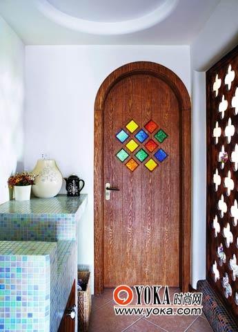 卫生间门上的彩色玻璃与屏风的雕花两两呼应,色彩上同样与马赛克贴面装饰保持一致,这个开敞式的卫生间是玄关与客厅的过渡,是功能多变的灰空间。